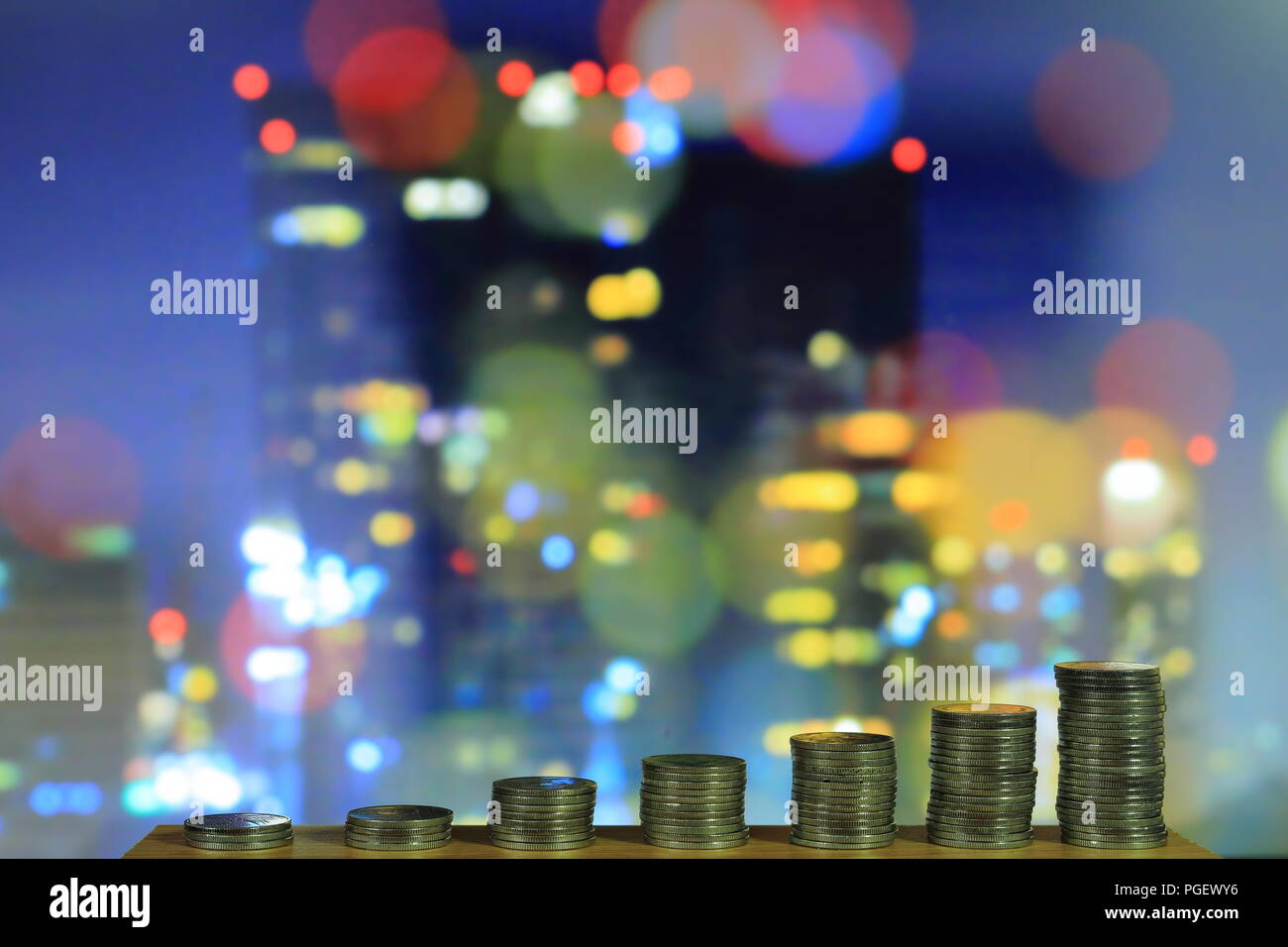 city of money. currency make metropolis go round. growing chart coin towers on wood board in front of defocused city scene at night. saving money - Stock Image