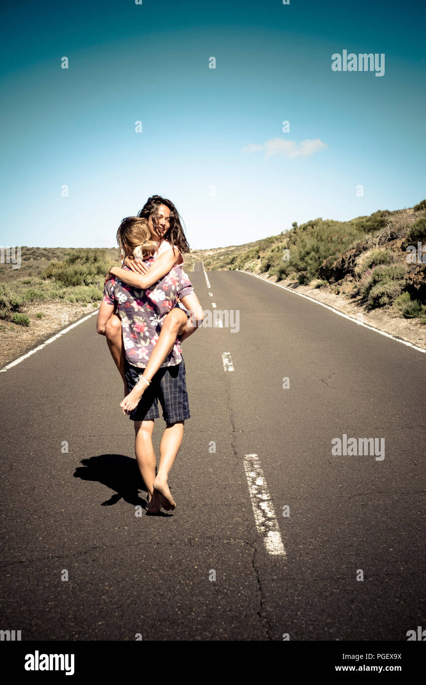 caucasian man viewed from rear carry a beautiful joyful girl on his chest and walk barefoot on a long asphalt road in the middle of the mountain. trav - Stock Image