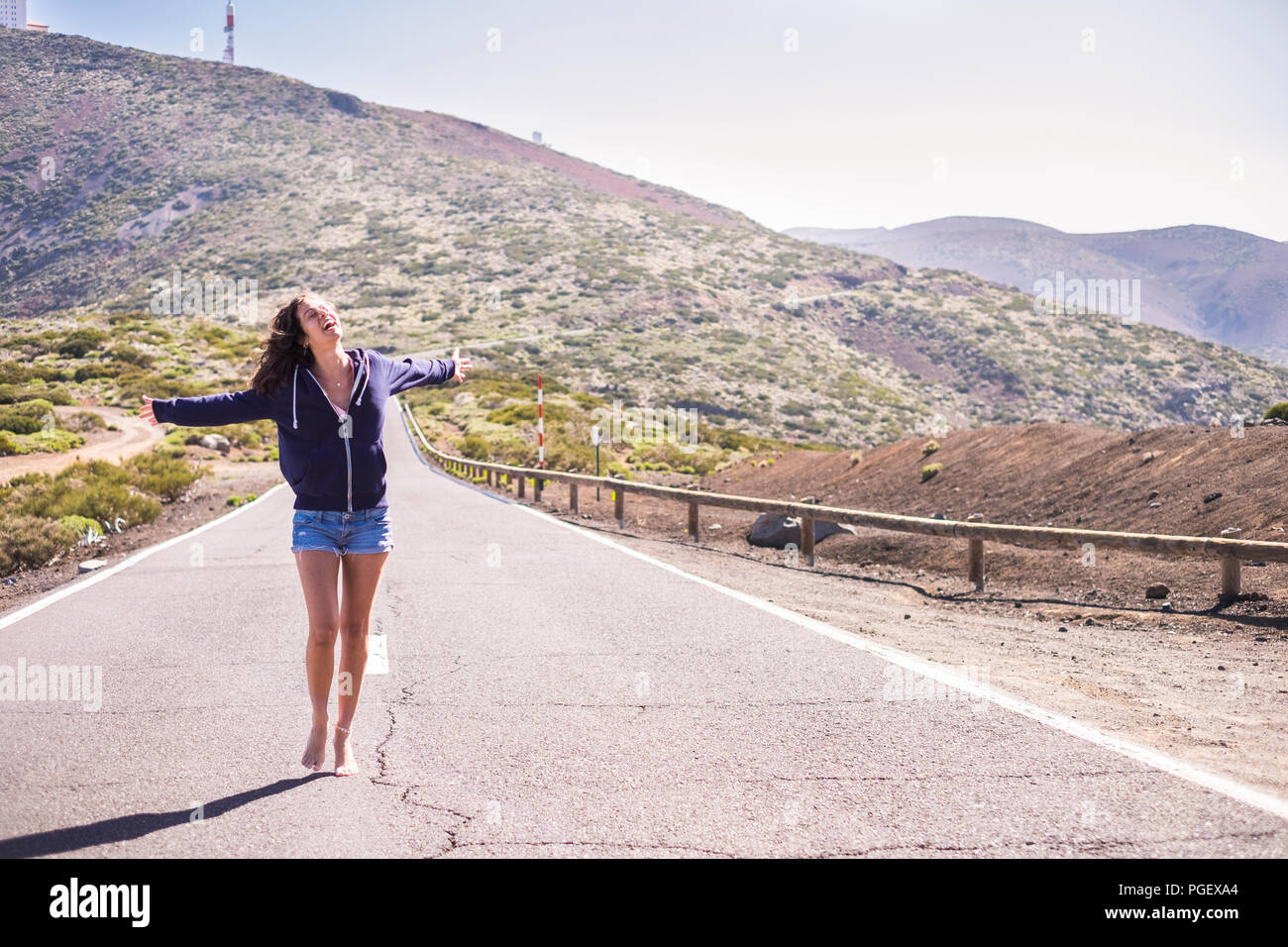 beautiful young woman walk barefoot over a long way road at the mountains. happiness and joyful concept for caucasian model with nice legs and shorts. - Stock Image