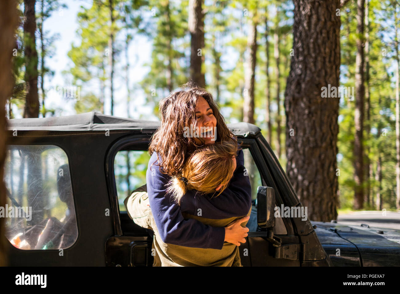 happiness during outdoor leisure activity for caucasian young couple in love and friendship. the woman hug the man laughing a lot and enjoying the lif - Stock Image