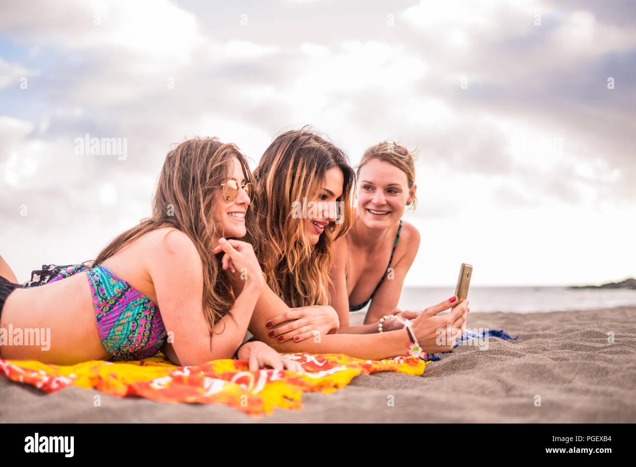 Pretty group of young females girl using a smart phone lying on the beach with the sea and horizon in the background. cheerful people enjoying the lif - Stock Image
