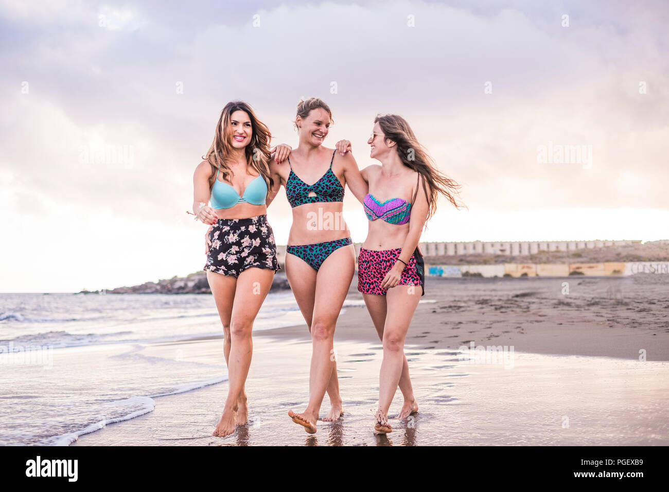 Portrait of three young female friends walking on the sea shore looking at camera laughing. Happy people enjoying vacation and seaside tropical beach  - Stock Image