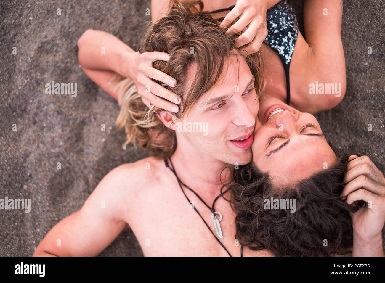 attractive couple of cheerful real people lay down at the beach in tenderness and love. bikini and summer style leisure activity for man and woman you - Stock Image