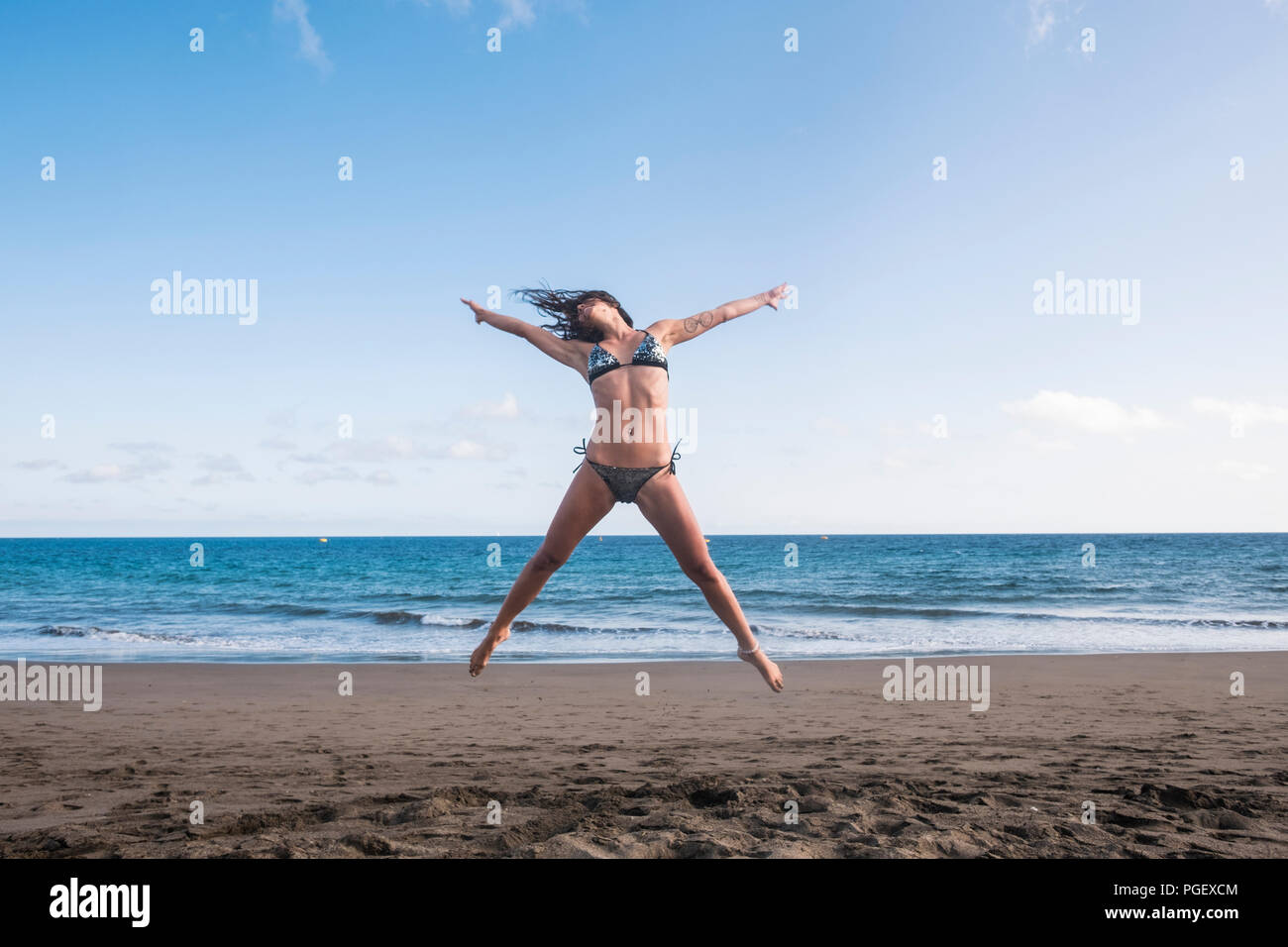 beautiful body fitness lifestyle young woman jump full of happiness at the beach near the shore and the waves of the blue ocean. joyful and summer fun - Stock Image