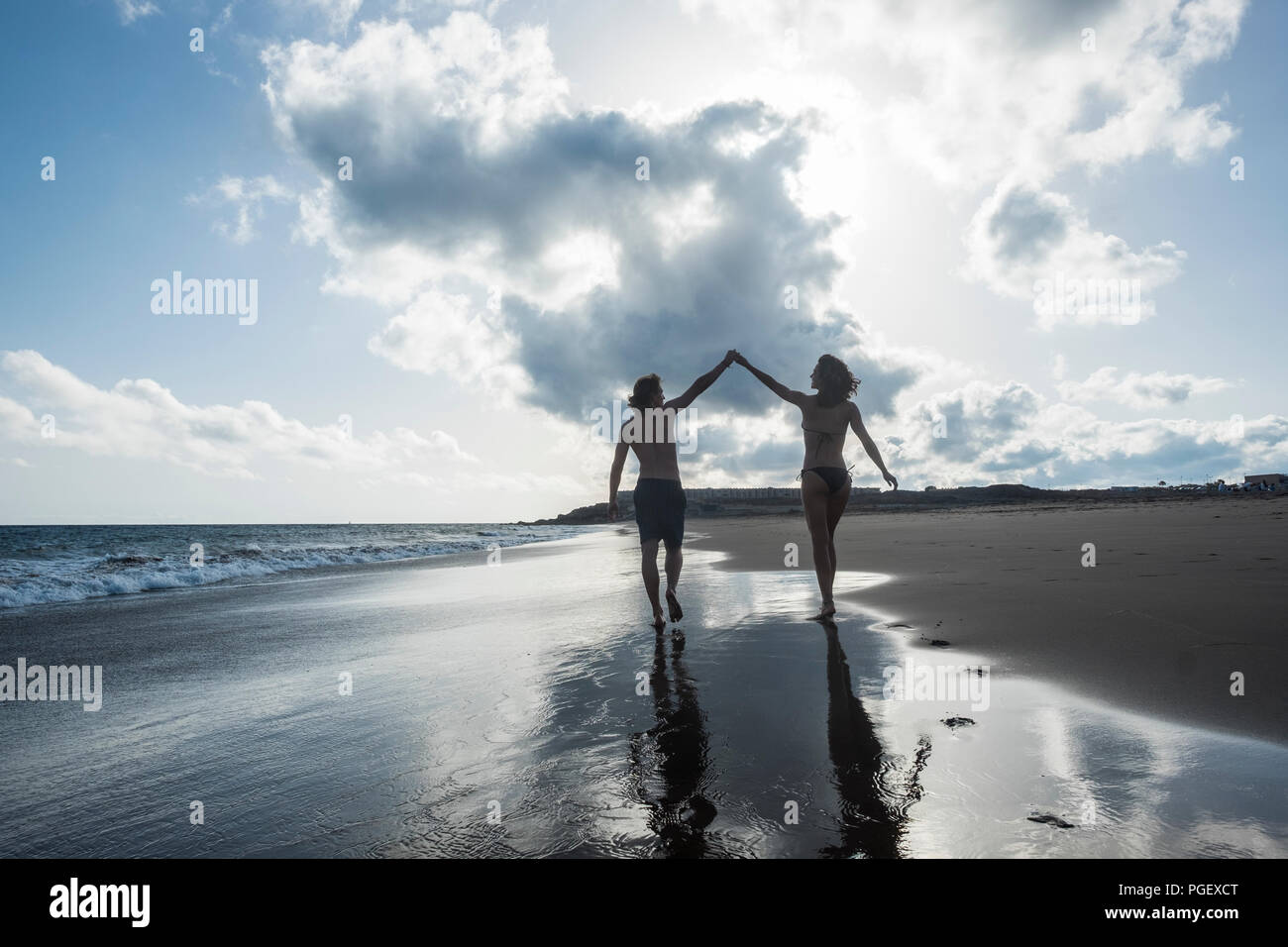happiness and joyful concept for couple of young beautiful people viewed from back walking on the shore touching the hands eachother. love and friends - Stock Image