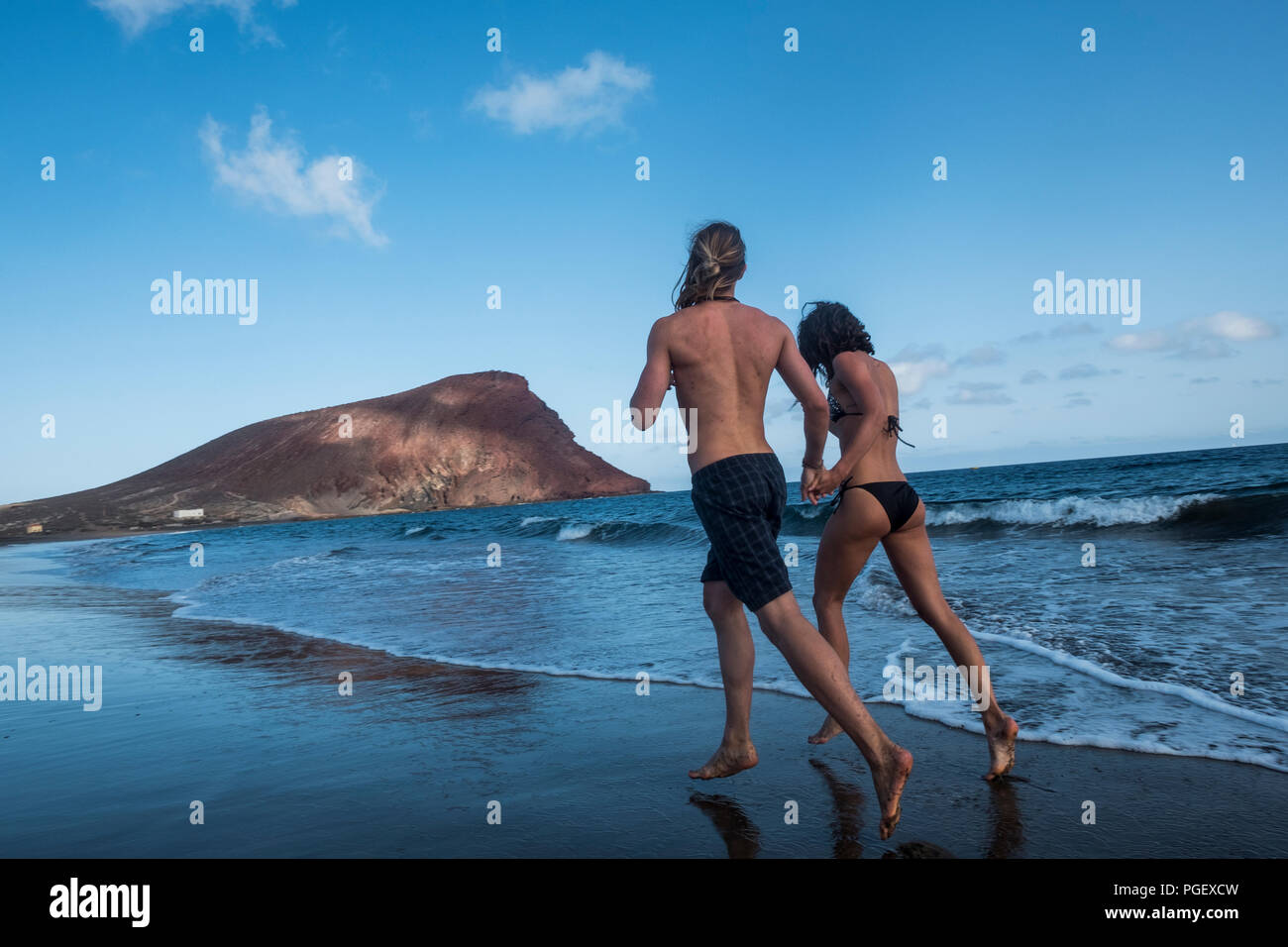 couple of young man and woman running on the beach near thw ocean. outdoor leisure activity for happy couple of traveler during summer holiday. beauti - Stock Image