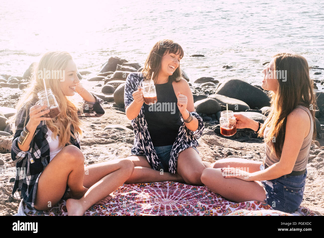 group of females friends sitting and enjoying the leisure activity during a summer vacation at the beach near the ocean. smiles and cheerful people ha - Stock Image