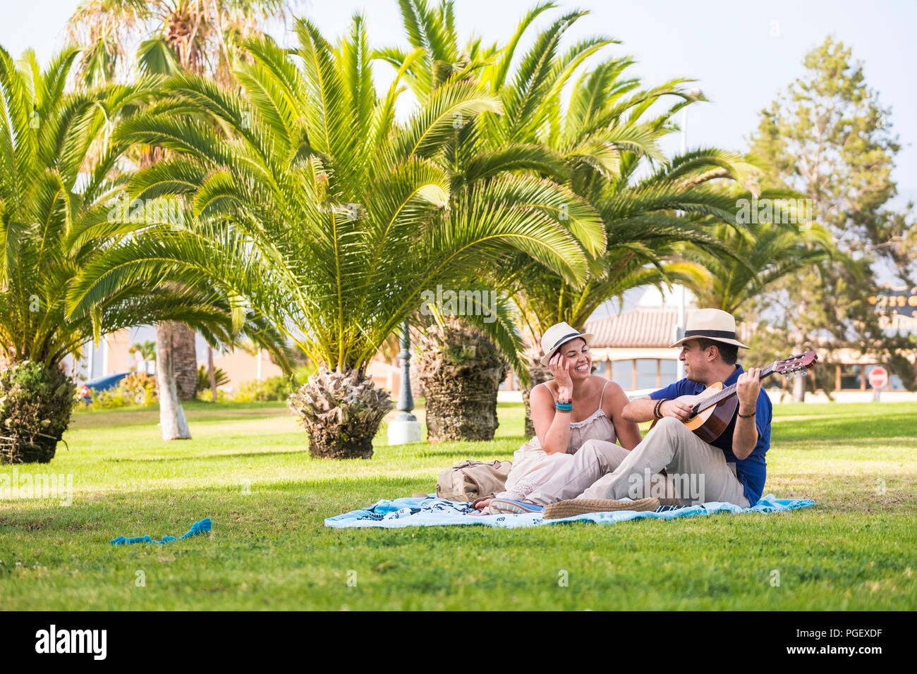 caucasian people sitting on the grass enjoying the weekend or the leisure activity together. tha man play an acoustic guitar and the girl look him wit - Stock Image