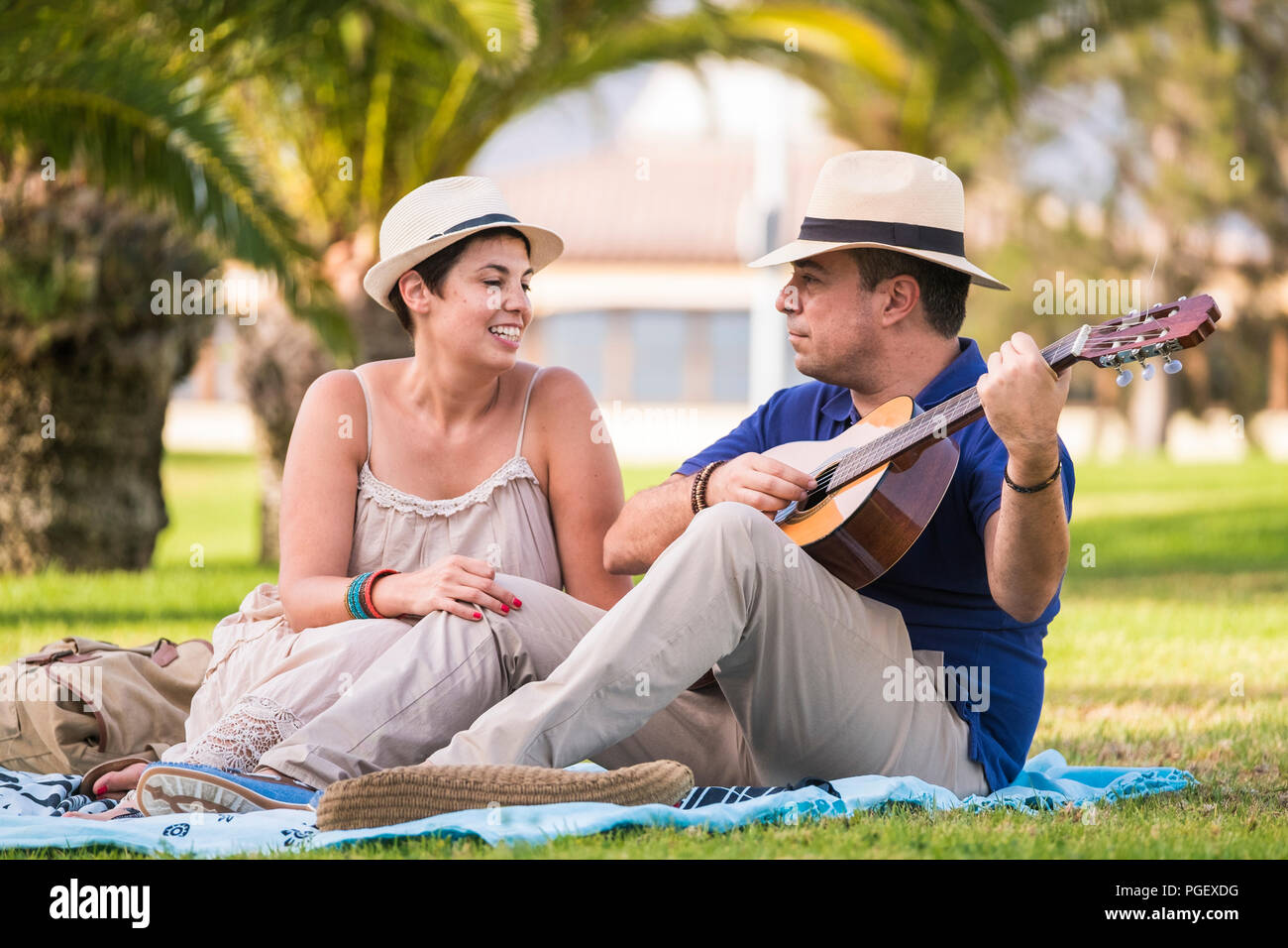 nice happy alternative couple enjoy the outdoor leisure activity together with love and fun playing an acoustic guitar and singing some songs. sitting - Stock Image