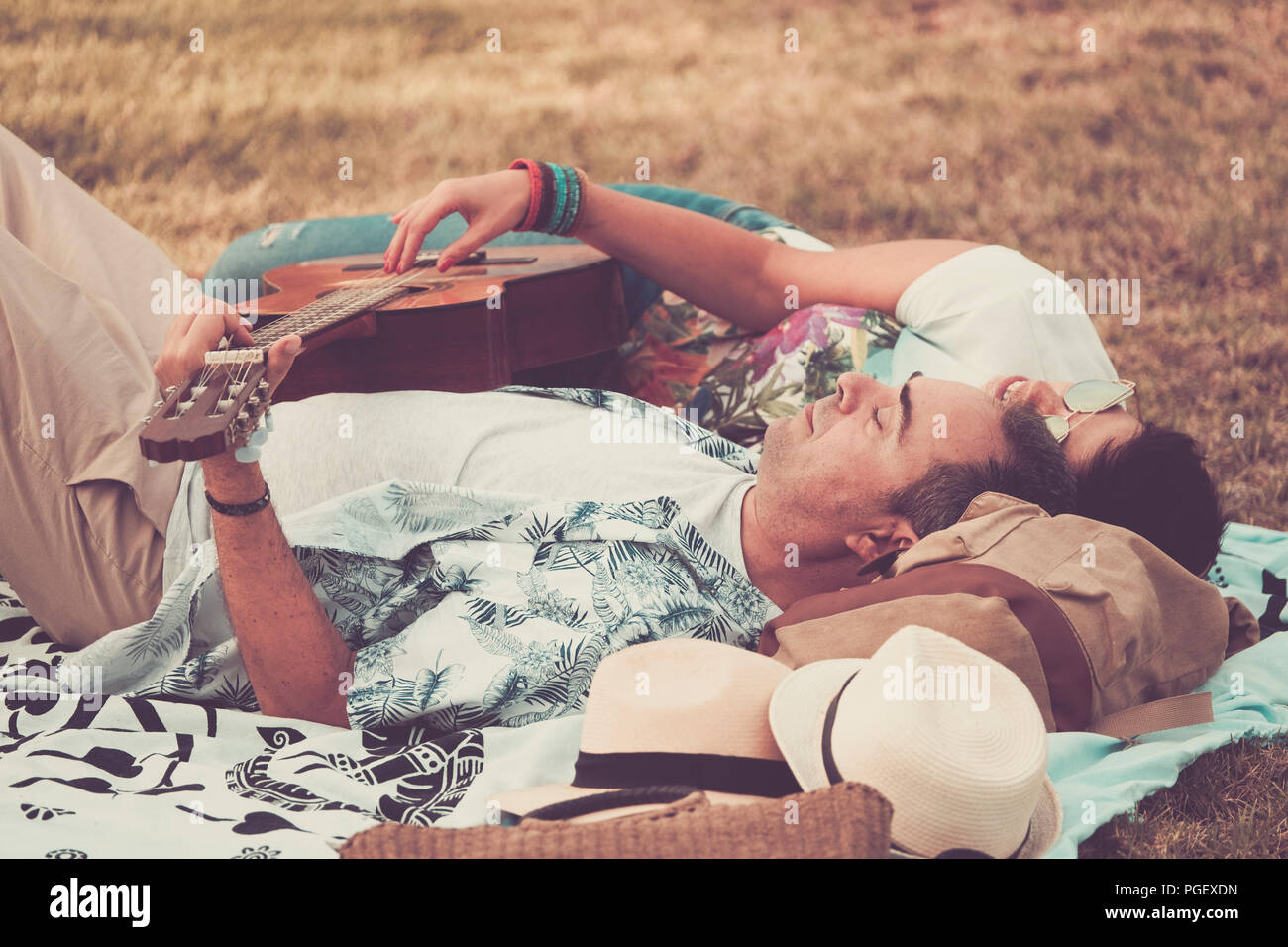 happy and relaxed cheerful couple laying down on the natural grass and enjoy the outdoor leisure activity with a good weather in spring season. man pl - Stock Image