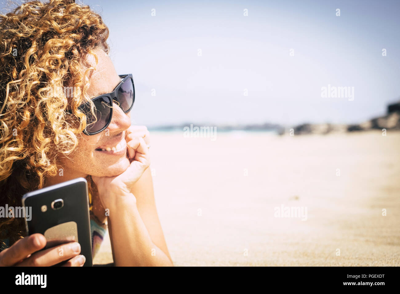 cheerful and attractive young woman lay down on the white sand at the beach in paradise resort vacationo and enjoy the holiday time. use phone to stay - Stock Image