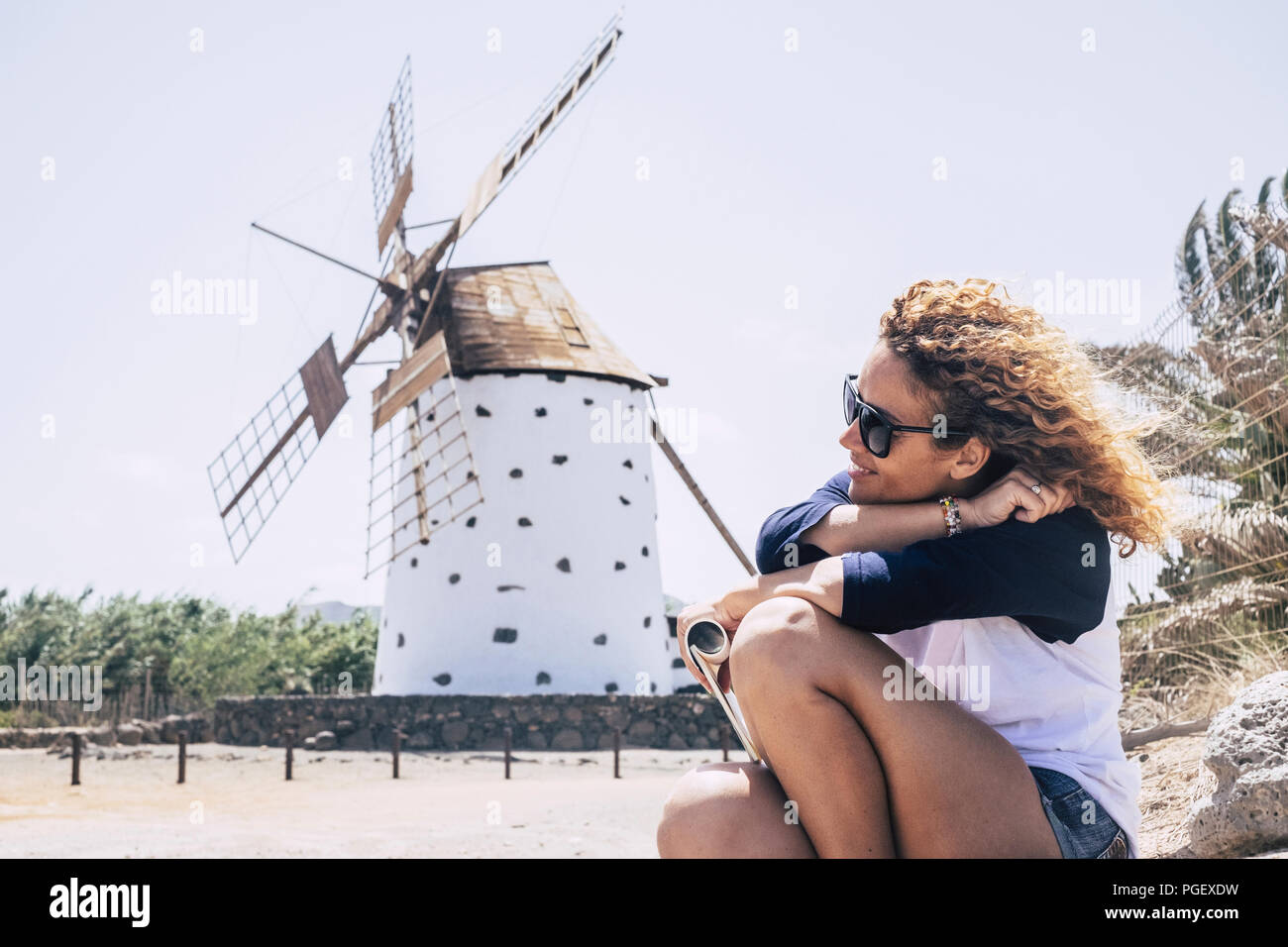 nice curly lady sitting and relaxing with sind in the hair and a wind mill on the background. country side scenic place for peace and relaxation conce - Stock Image