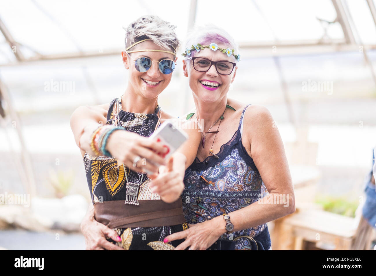 hippy couple of caucasian beautiful females use a smart phone. Different ages  nice attractive people stay together in happy leisure activity with fri - Stock Image