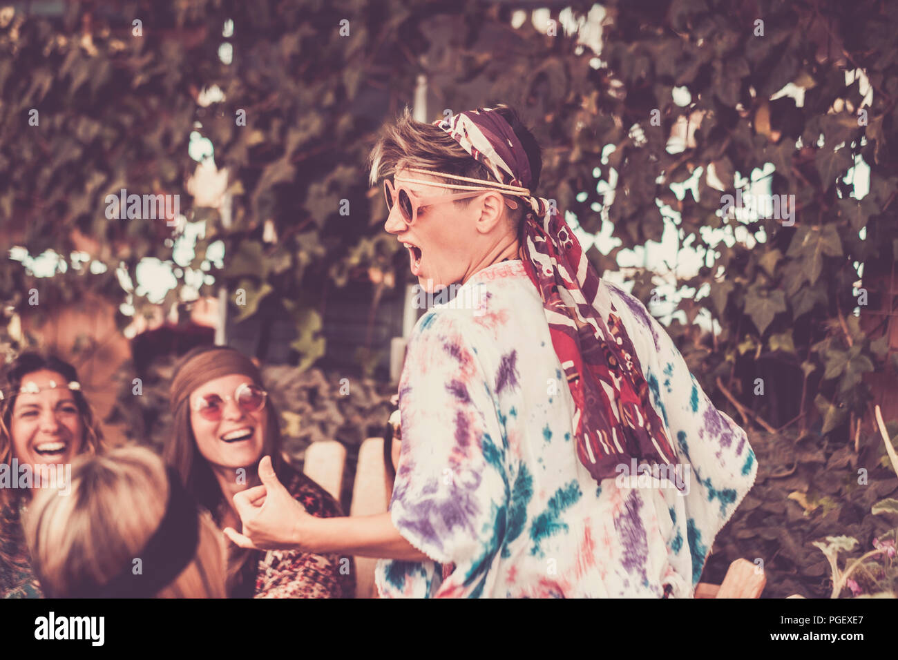 crazy blonde young woman and girls in friendship all together celebrating and having fun in a bio natural place. smiles and laughing for group of hipp - Stock Image