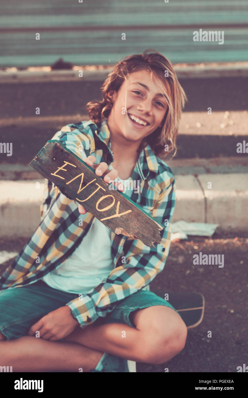young beautiful male teenager take a piece of wood wht enjoy written on it. positive vibes word for all the people. hand made painted. happy and peace - Stock Image