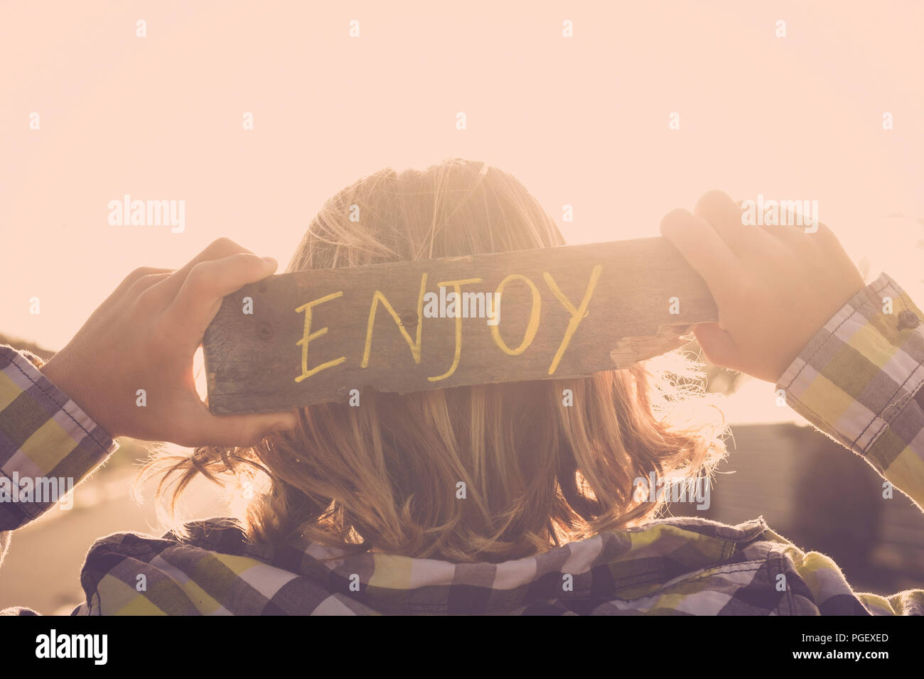 blonde people young teenager with enjoy written on a natural piace of recycled wood. feeling and golden sunset atmosphere image for positive life and  - Stock Image