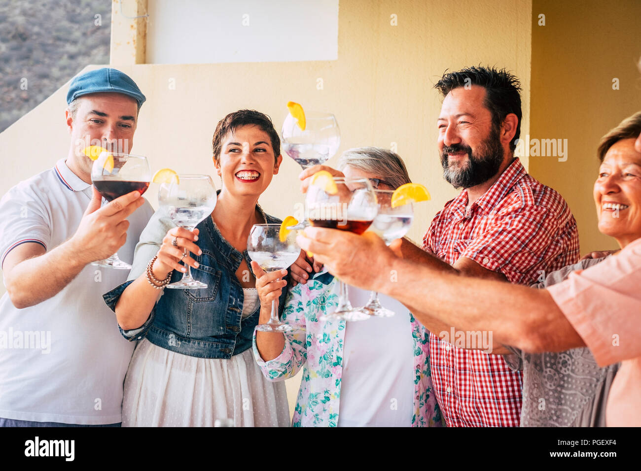mixed ages group of caucasian people having fun together celebrating an event drinking cocktail with red wine of white vodka. holiday concept with hap - Stock Image
