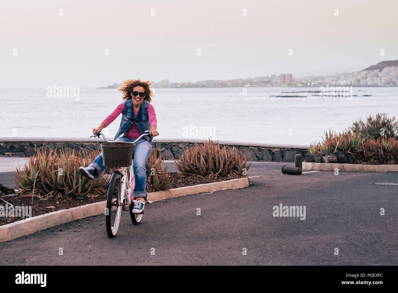 nice beautiful young caucasian woman with curl hair in the wind moved with a bike and have fun enjoying the leisure activity outdoor on a coastline ro - Stock Image
