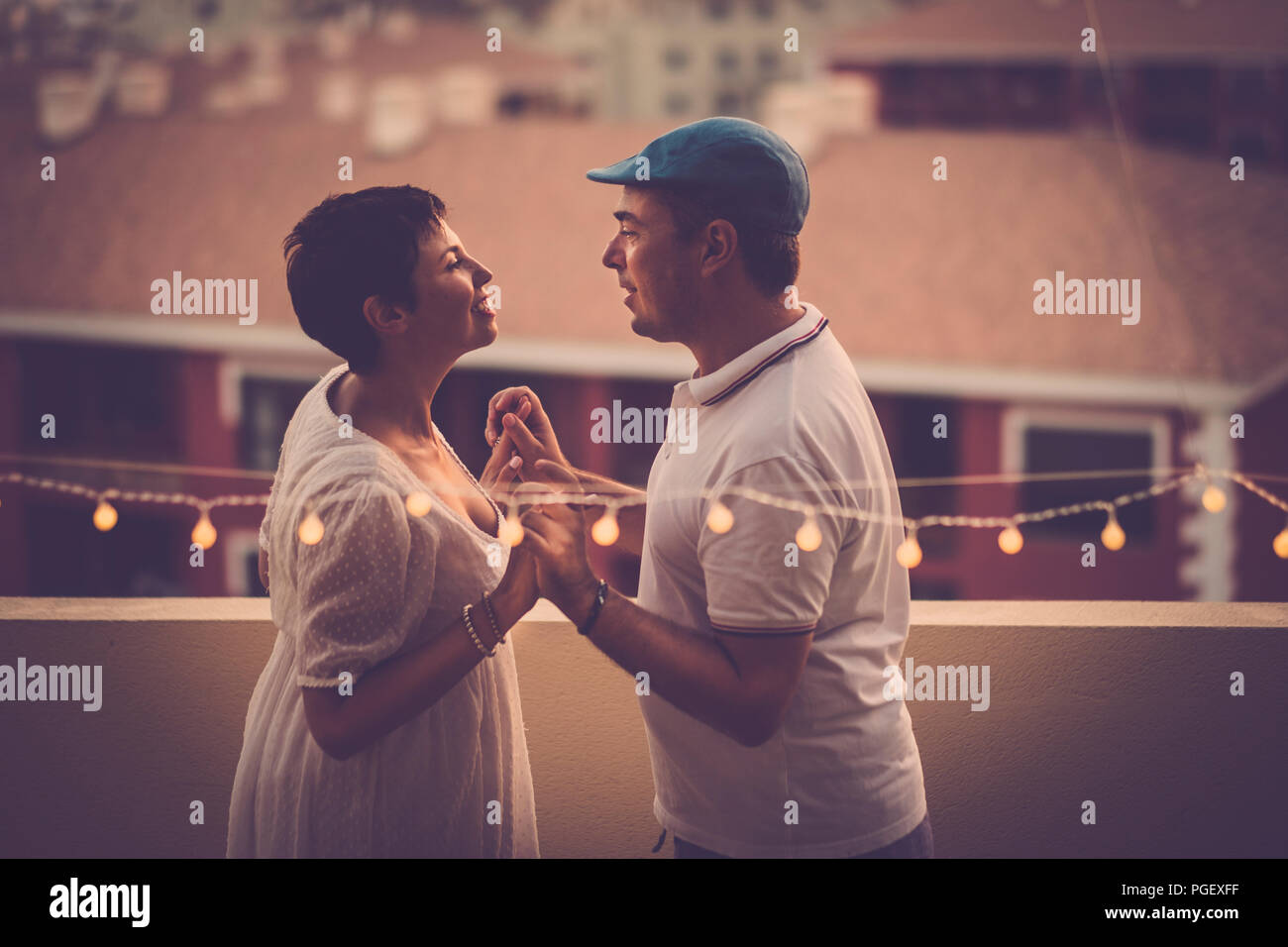 beautiful middle age couple in love smiling eachother and looking in the eyes at home in the terrace with amazing houese view from above. relationship - Stock Image