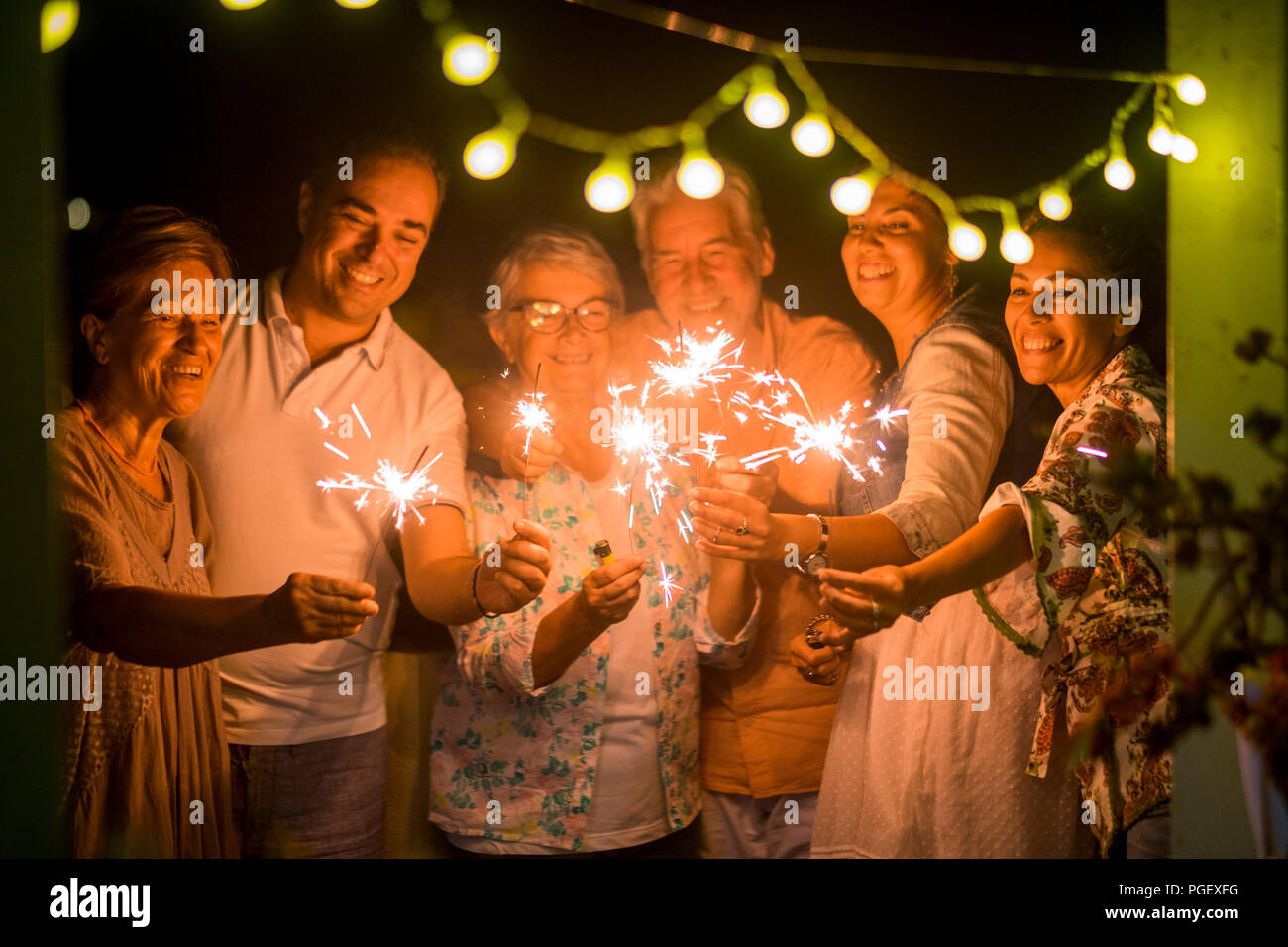 group of people celebrate an event like new years eve or birthday all together with sparkles light by night in the dark. smiles and having fun in frie - Stock Image