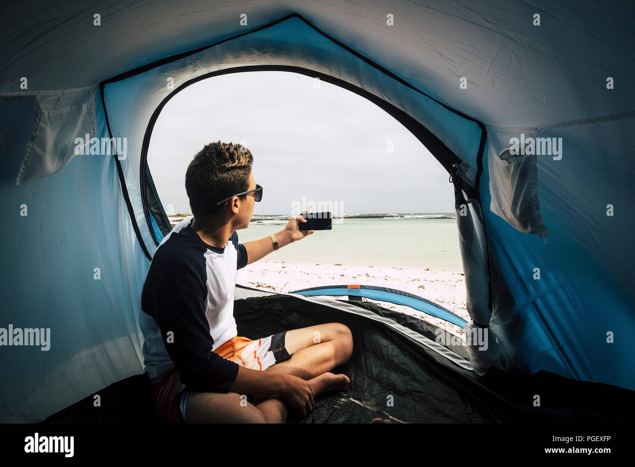 young teenager handsome boy camp directly on the white beach in tropical heaven place islands. from the door of the tent take a picture with the phone - Stock Image