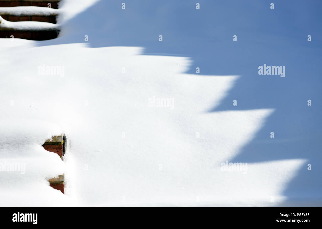 Snow, sunshine and shadows in a tiered garden. - Stock Image