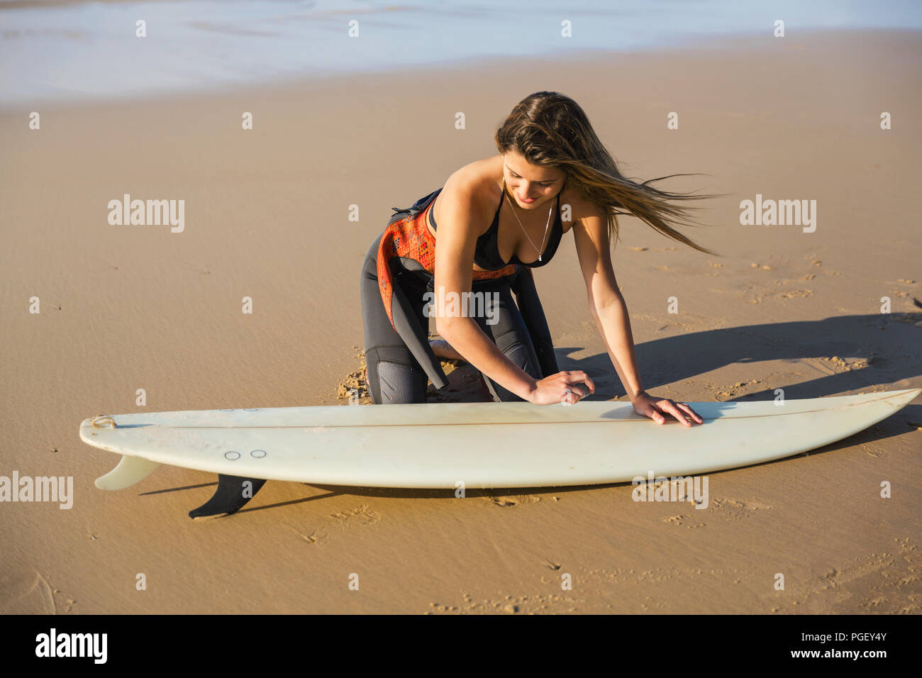 Two beautiful surfer girls at the beach getting ready for surfing - Stock Image