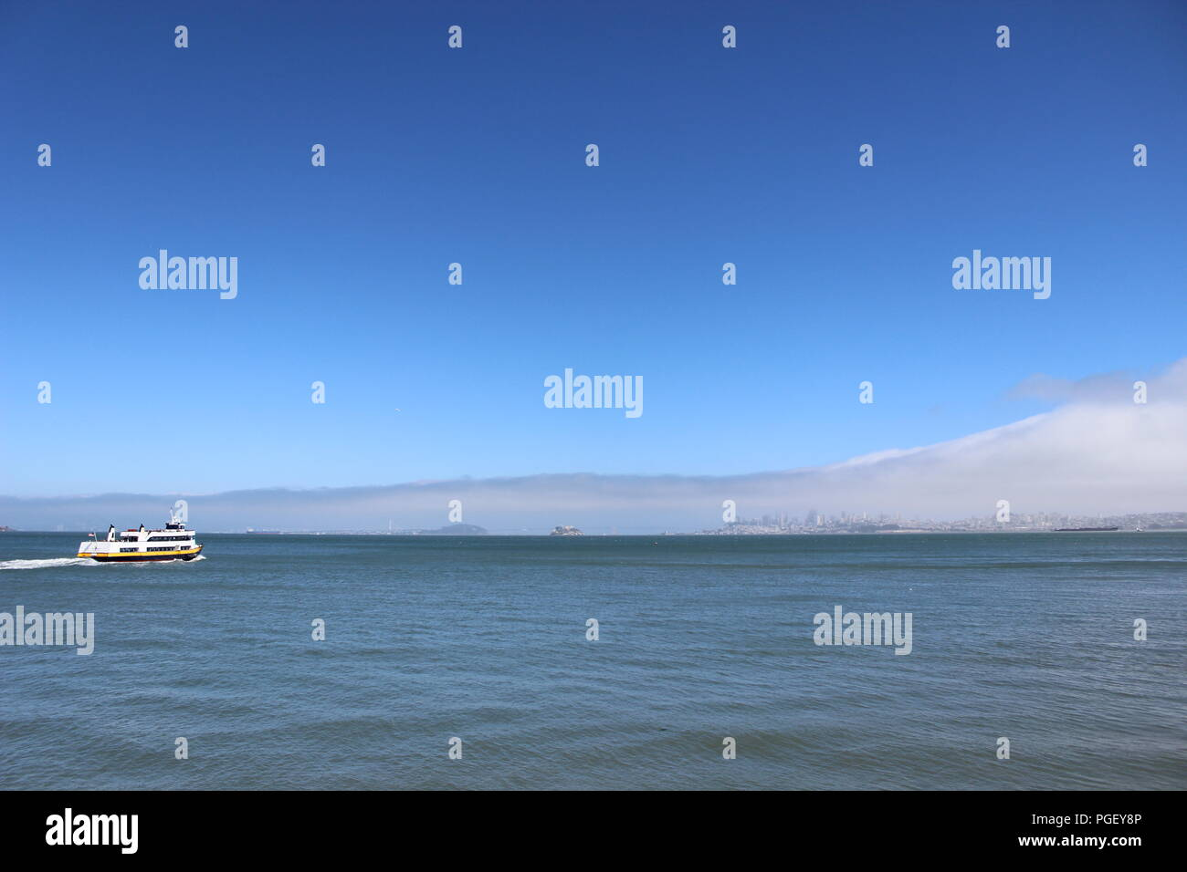 A Sausalito ferry boat heads towards a foggy San Francisco, California, USA - Stock Image