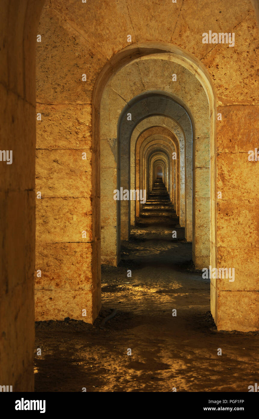 Passageway of arches known as the Keyhole Gallery, La Mola, Menorca, Spain. The passage seems to go on for ever with countless arches - Stock Image
