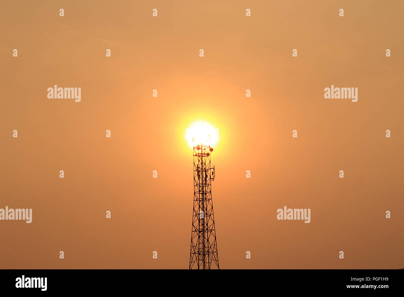 The sun shines behind the telephone tower at the top of the tower. - Stock Image