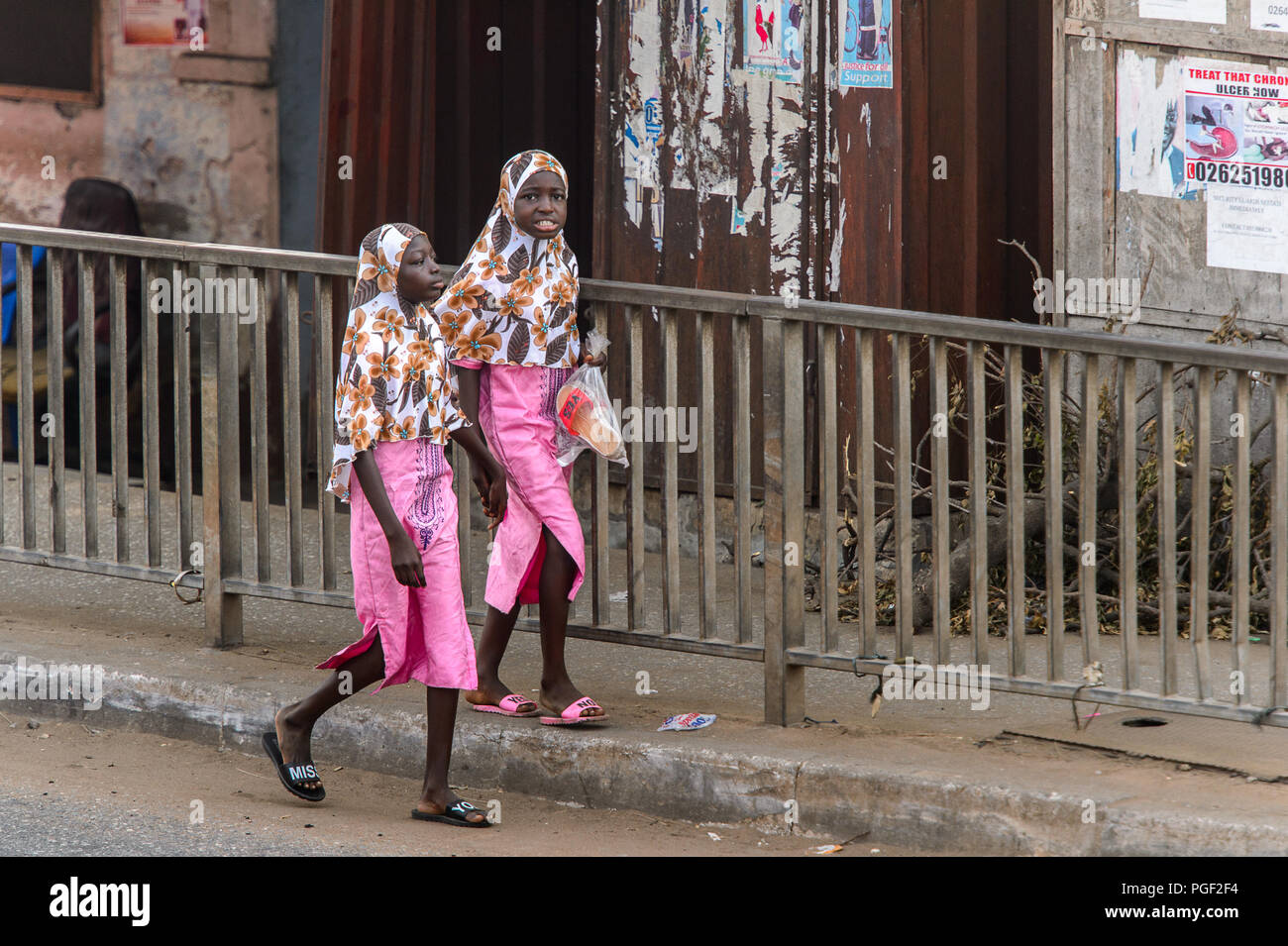 ACCRA, GHANA - JAN 8, 2017: Unidentified Ghanaian two girls wear hijab and pink skirts . Children of Ghana suffer of poverty due to the economic situa - Stock Image