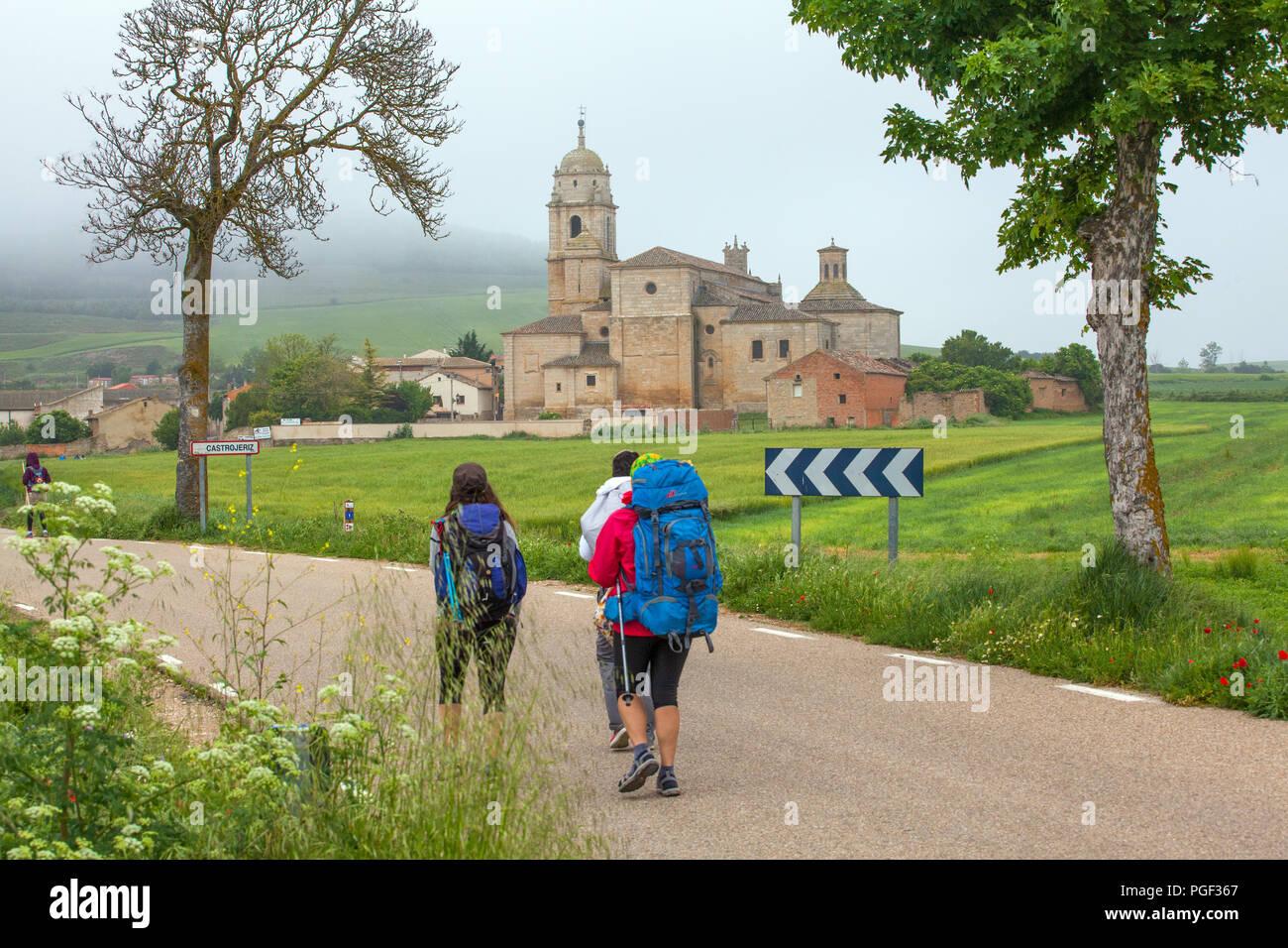 Pilgrims man and woman near the Colegiata de Santa Maria del Manzano while walking the Camino de Santiago the way of St James Castrojeriz Spain - Stock Image