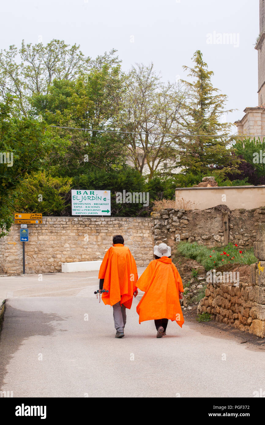 Two pilgrims walking the Camino de Santiago the way of St James wearing  waterproof clothing Cagoules / ponchos approaching the town of Castrojeriz - Stock Image