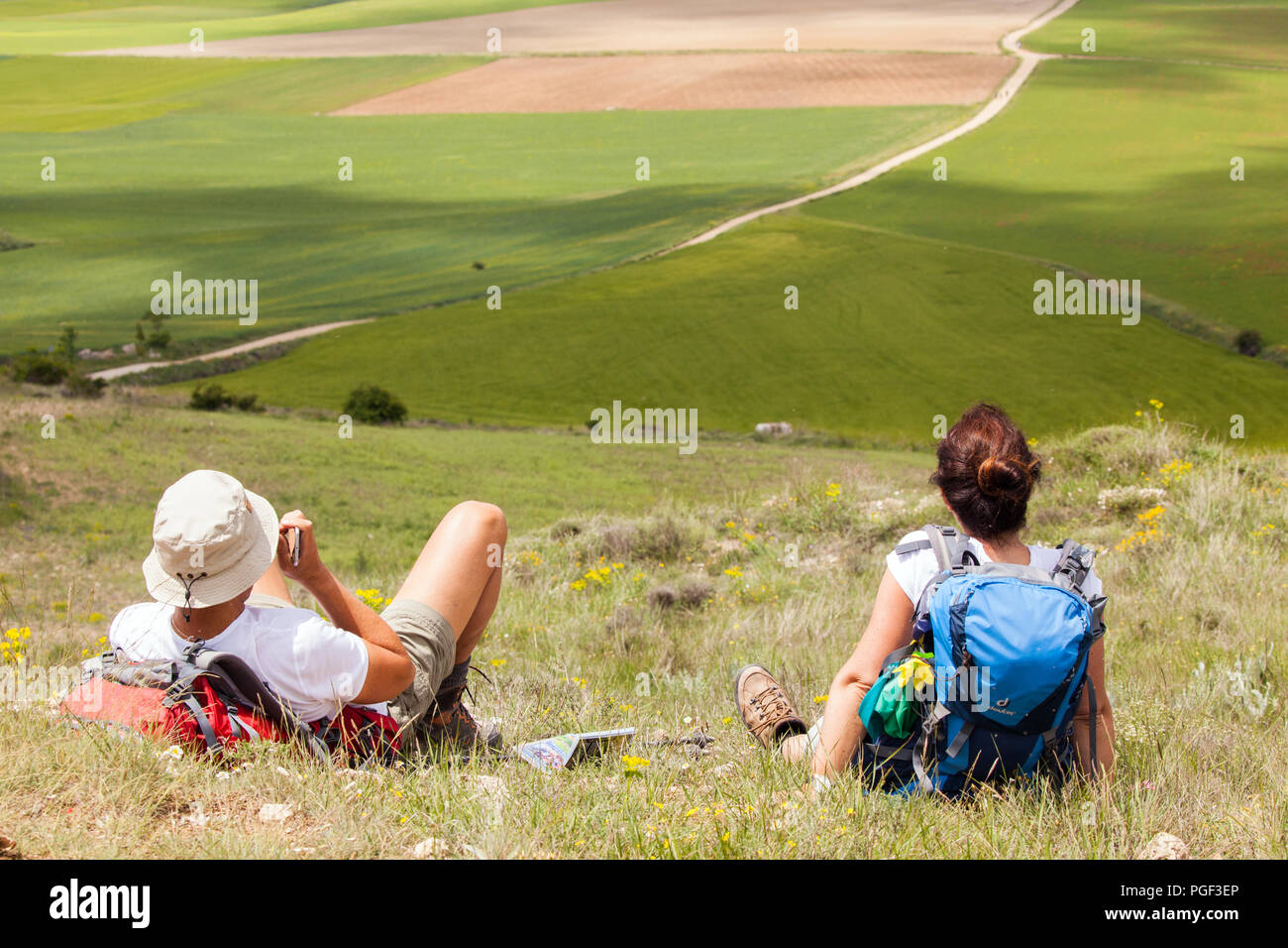 Man and Woman pilgrims resting while walking on the way of St James the Camino de Santiago on the Alto Mostelares between Castrojeriz and Fromista - Stock Image
