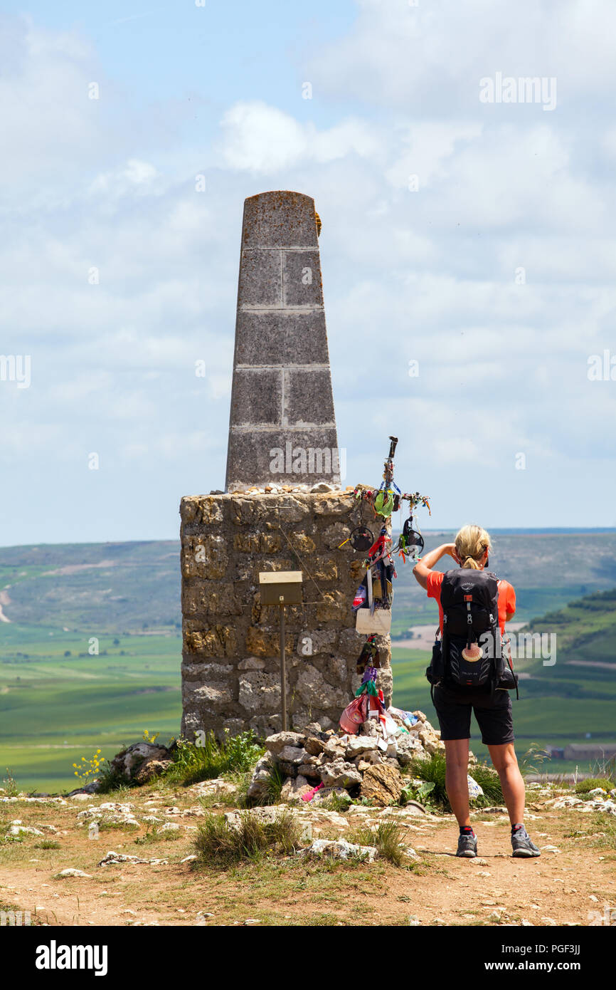 Woman on the Camino de Santiago the way of St James stopped to take a photograph of the memorial stone monument at the top of the Alto de Mostelares - Stock Image