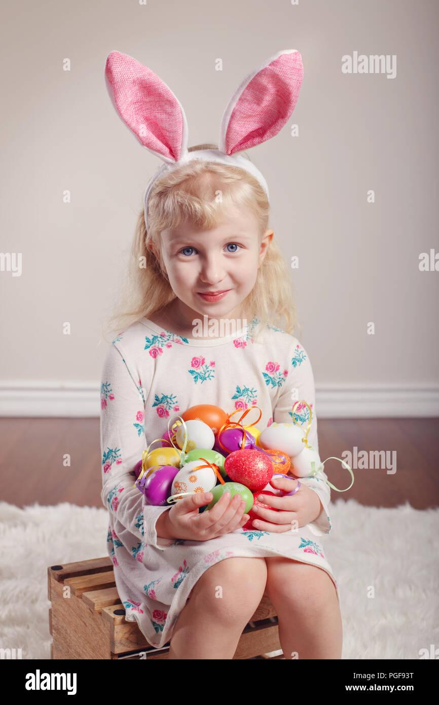 e6cec2b1b96 Cute adorable Caucasian child girl wearing Easter bunny rabbit ears sitting  on wooden box in studio