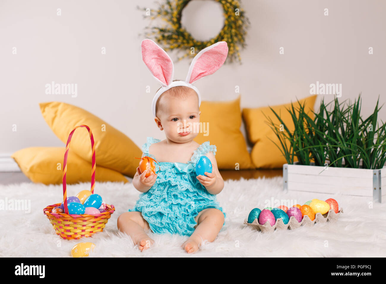 a5ef0e3d603 Cute adorable Caucasian baby girl in blue green romper wearing bunny ears  sitting in studio. Kid child playing with Easter colorful eggs celebrating t