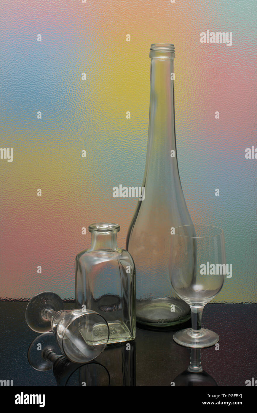 A harmonious still life arrangement of transparent bottles and wine glasses on a black glass and a vertical textured one with colors in the background - Stock Image