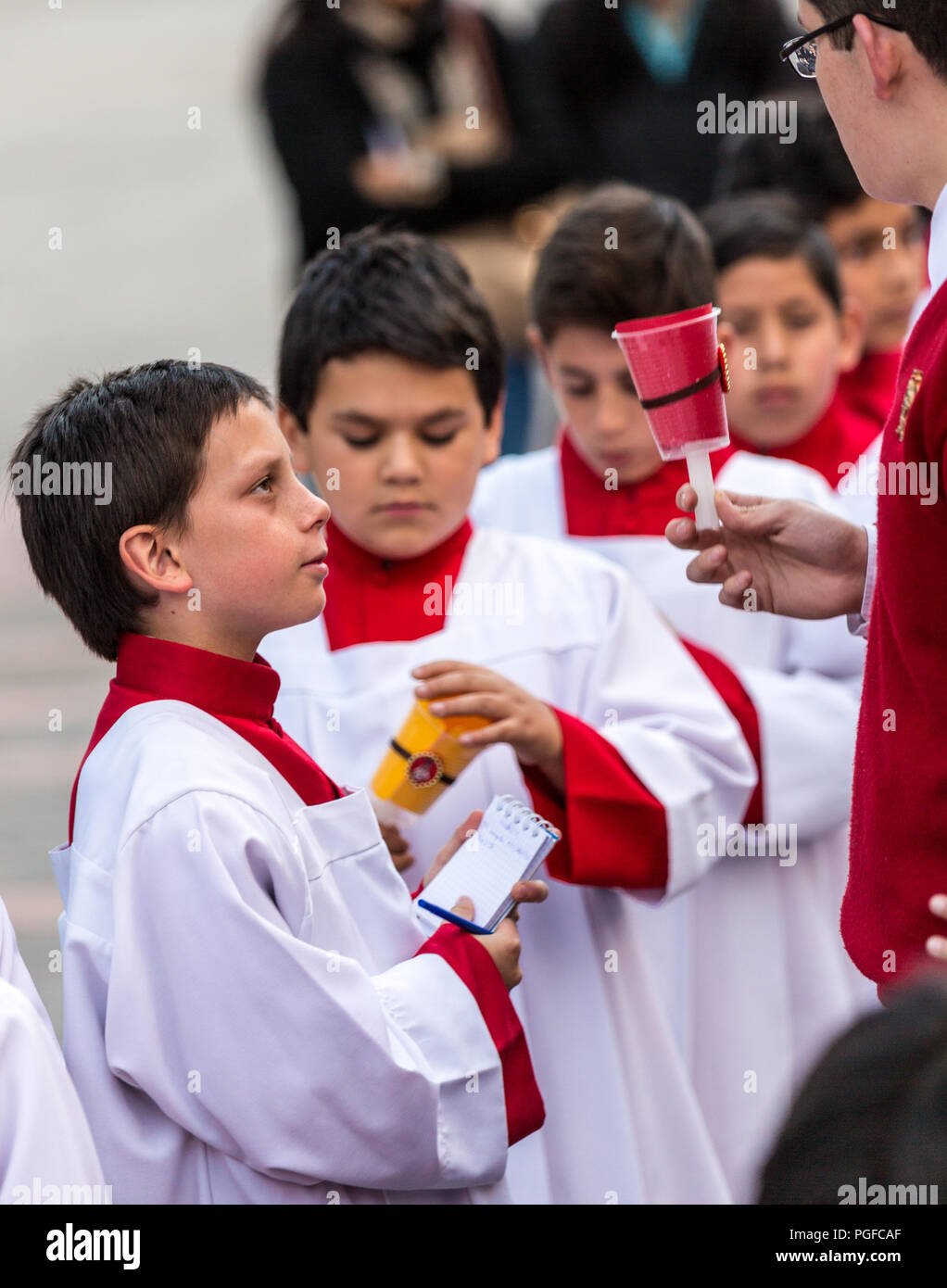 Cuenca, Ecuador / June 4, 2015 - Catholic Curate (priest trainee) talks to young boys prior to Corpus Cristi procession - Stock Image