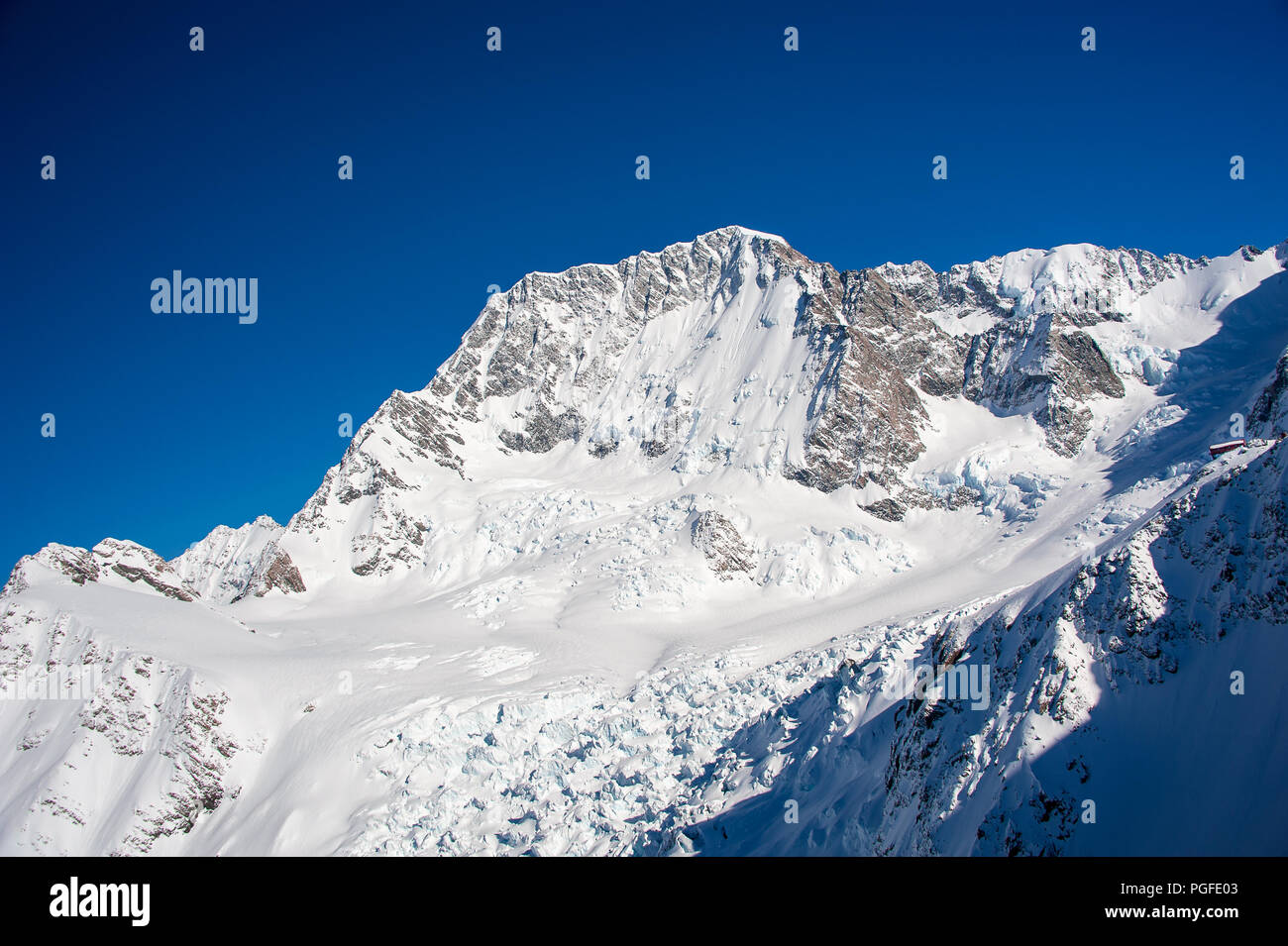 Aerial view to the Mueller Hut on Mt Ollivier, the Mount Cook National Park, New Zealand. Spectacular scenery with red lodge perched on a snowy rise - Stock Image