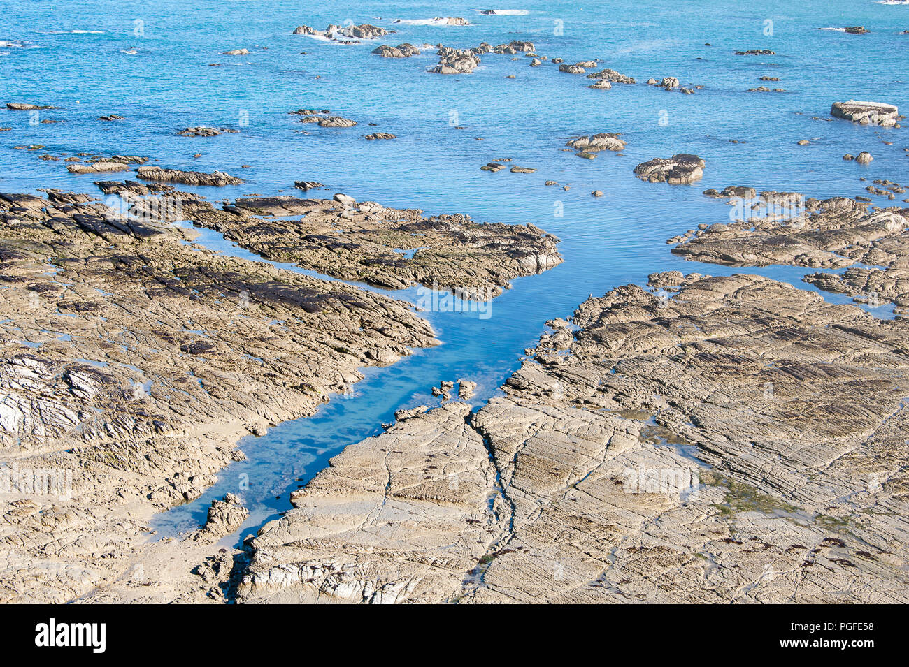 Aerial view to exposed rocks along shoreline. Turquoise sea contrasts with sandy coloured limestone shelf - Stock Image