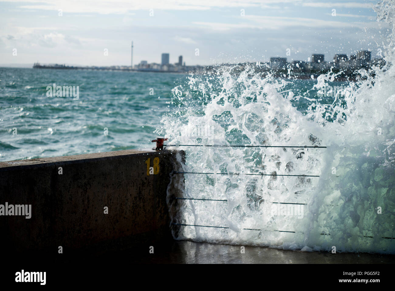Waves smashing against Brighton Marina wall with Brighton Pier and i360 in the background. - Stock Image
