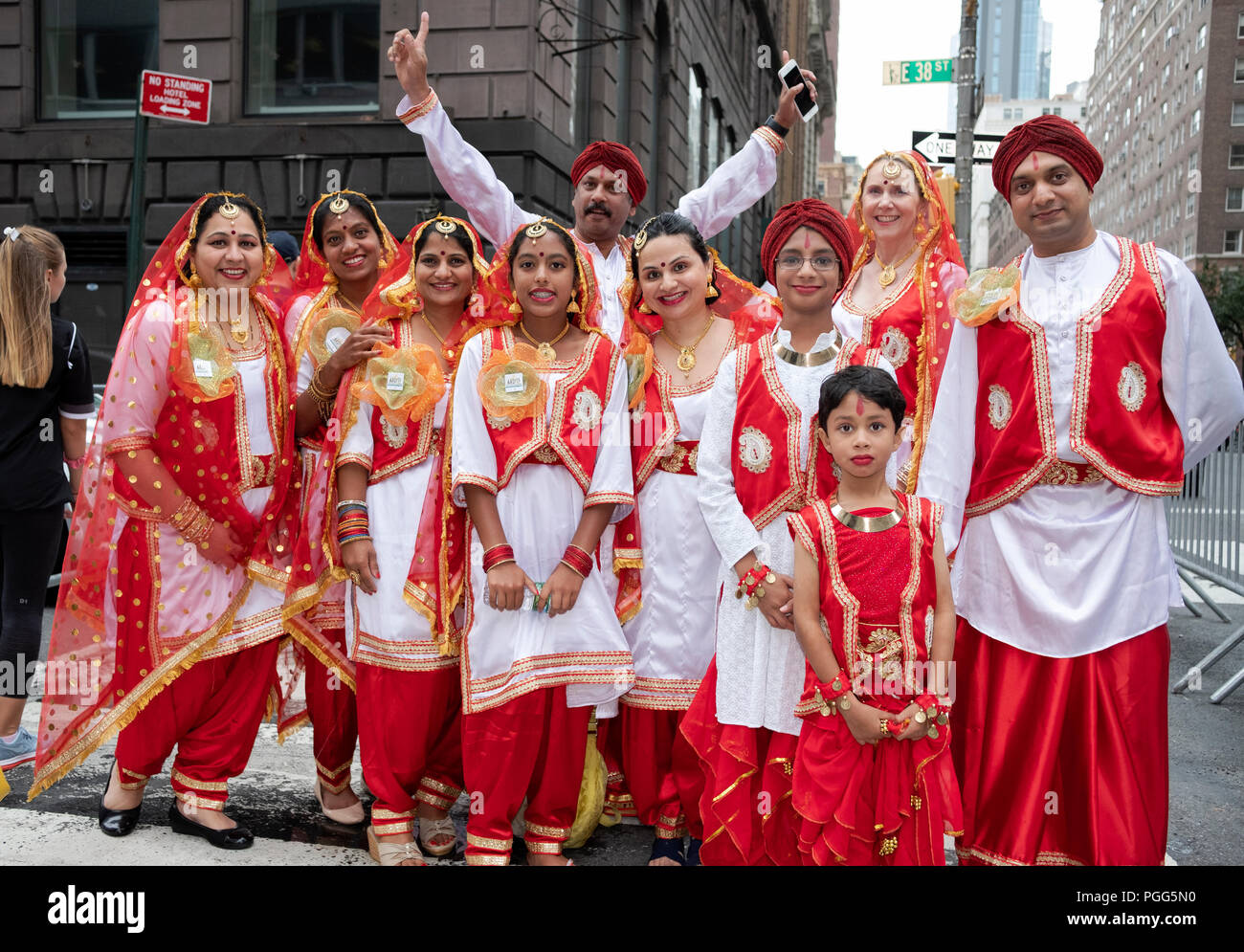 A extended family in matching red & white costumes at the 2018 India Day Parade in New York City. - Stock Image