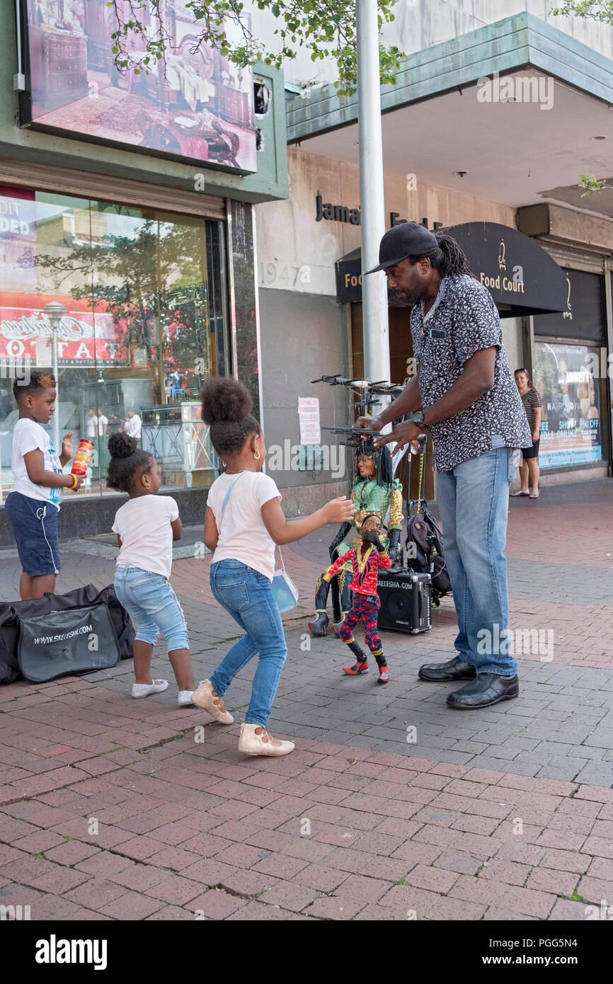 A marionette puppeteer entertaining children at the 165th Street Pedestrian Mall in Jamaica, Queens, New York. - Stock Image