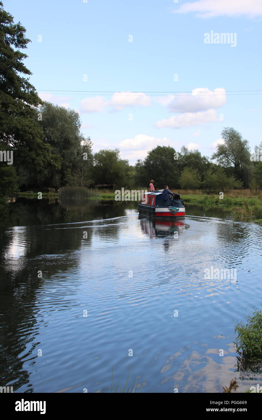rear view of a houseboat cruising down the river wey with blue sky and clouds - Stock Image