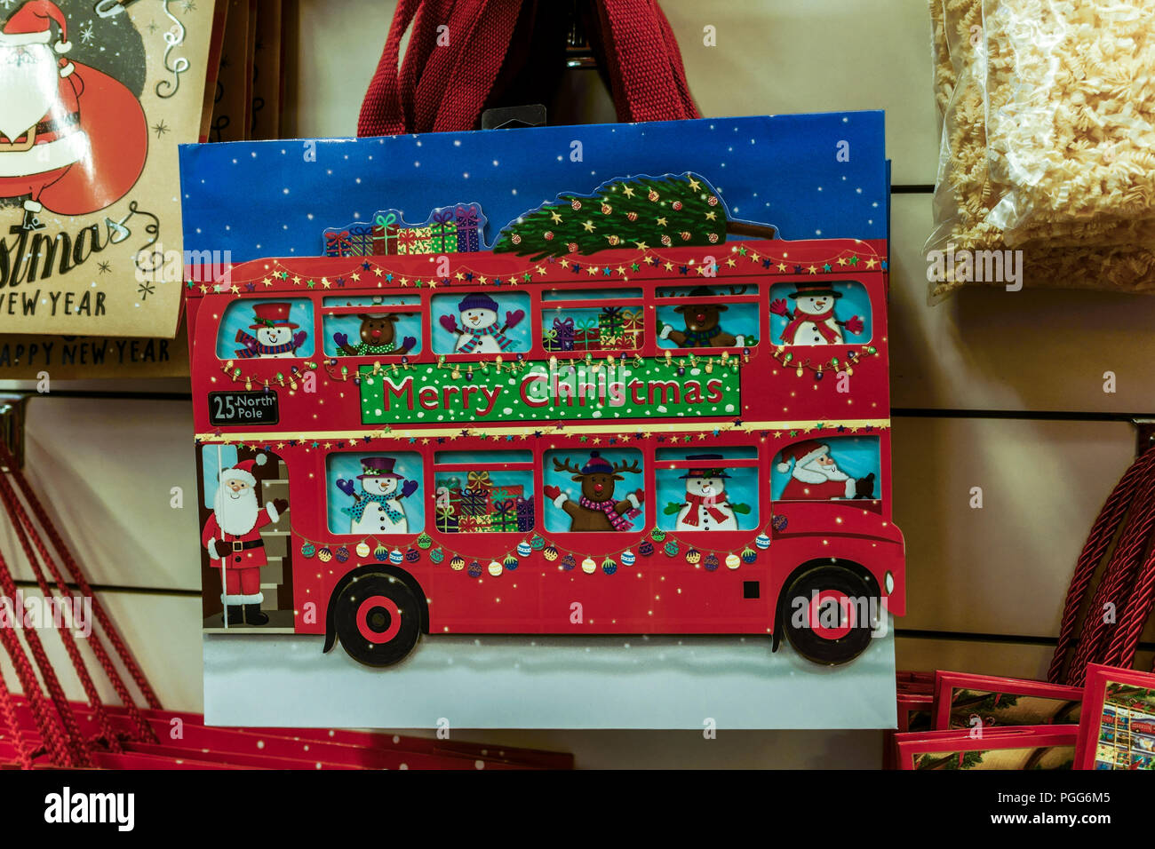 Merry Christmas red double decker bus drawn on a shopping bag on display in a shop. - Stock Image