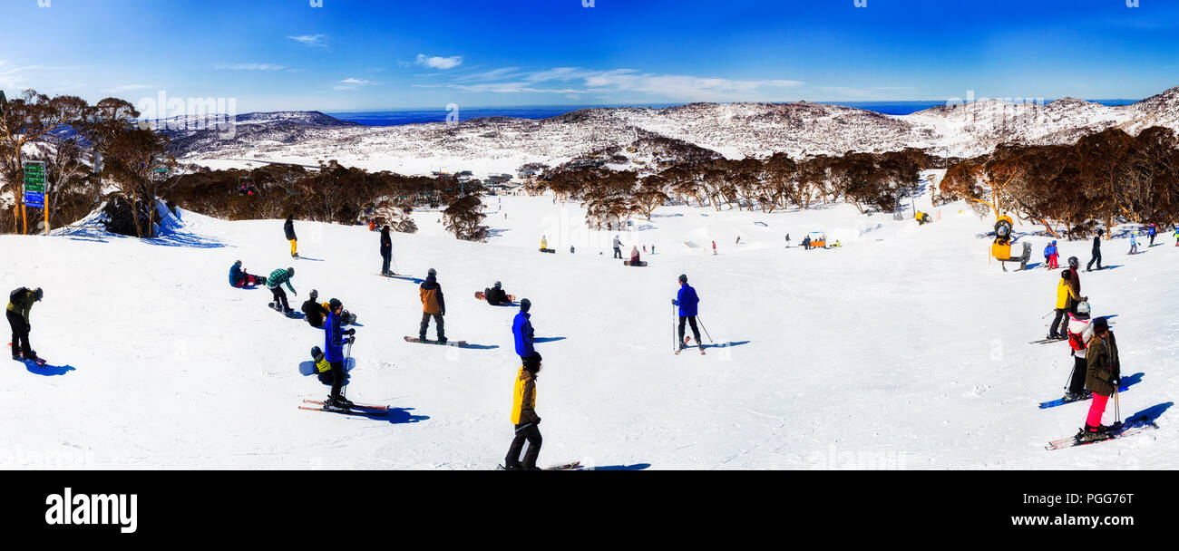 Skiers and snowboarders on snow covered slopes of Perisher ski resort from Back Perisher mountain down to the central valley on a sunny cold winter da - Stock Image