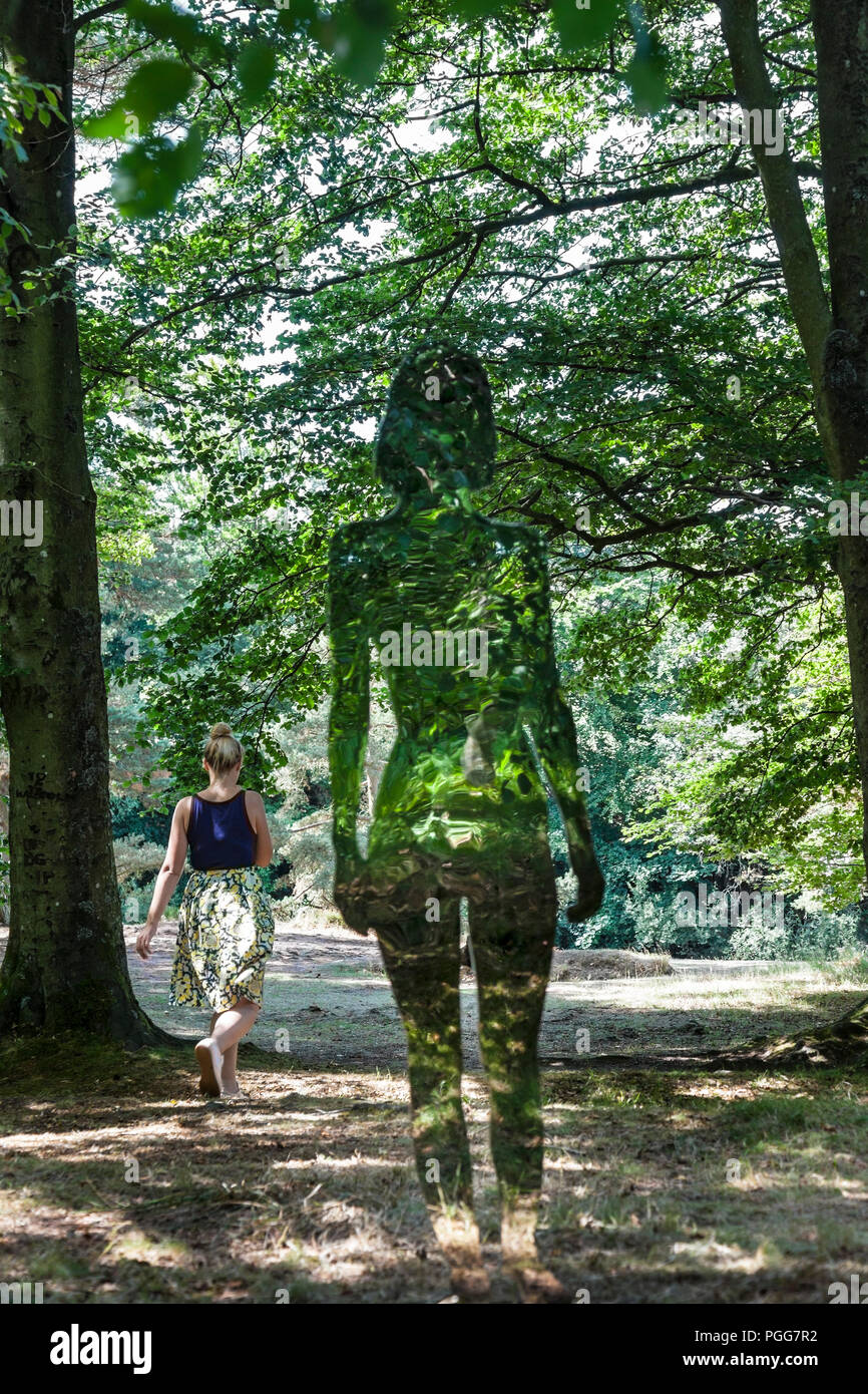 A Woman Walks Past One of the Highly Reflective 'Natural Creation' Art Figures Created by Artist Rob Mulholland at Low Force, Bowlees, County Durham,  - Stock Image