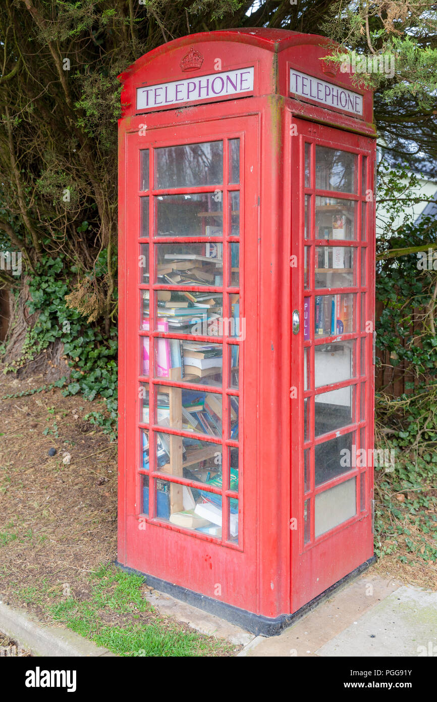 Red public telephone box in the UK. Phone booth full of books acting as a local mini library. Red phone boxes are very iconic in England and have been - Stock Image