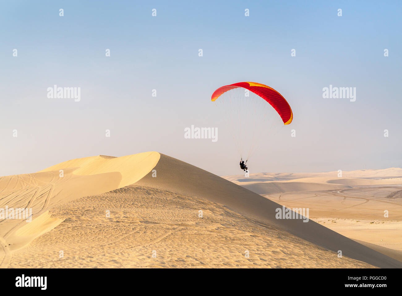 Unrecognizable paraglider flying over sand dunes in Qatar desert - Stock Image